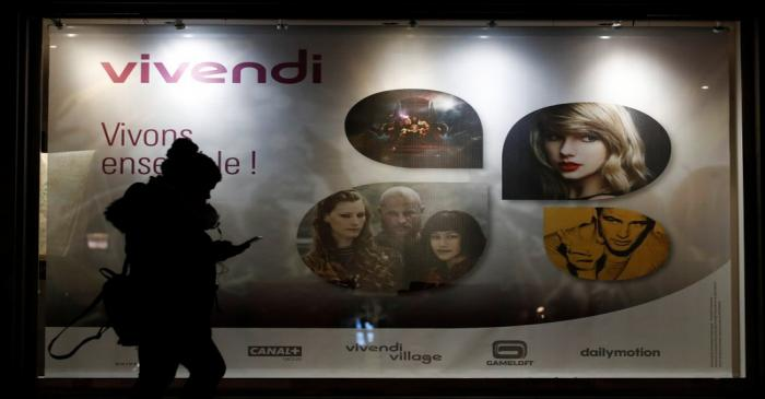 A woman walks pass by a sign of Vivendi at the main entrance of the entertainment-to-telecoms
