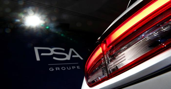 A PSA Group logo is seen behind a car displayed during French carmaker's news conference as