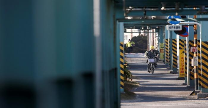 FILE PHOTO: A worker cycles near a factory at the Keihin industrial zone in Kawasaki