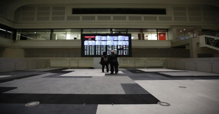 Visitors looks at an electronic board showing the Japan's Nikkei average at the Tokyo Stock