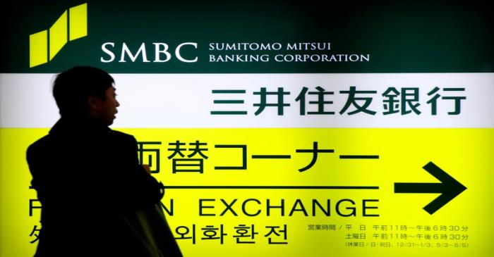 FILE PHOTO: A man walks past a sign board of Sumitomo Mitsui Banking Corporation, part of SMFG