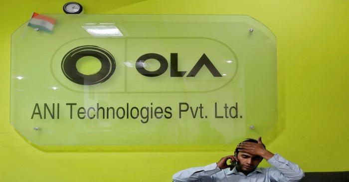 An employee speaks over his phone as he sits at the front desk inside the office of Ola cab
