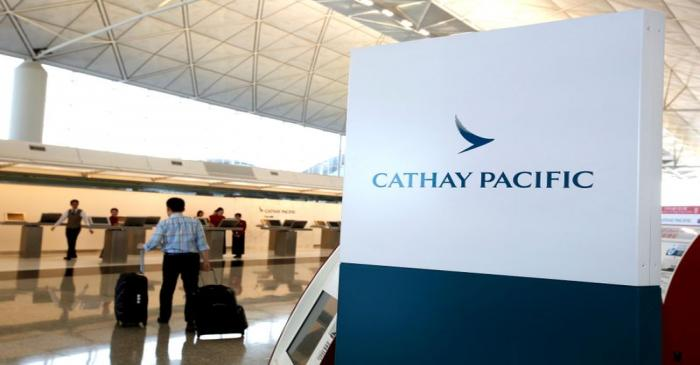 A passenger walks to the First Class counter of Cathay Pacific Airways at Hong Kong Airport in