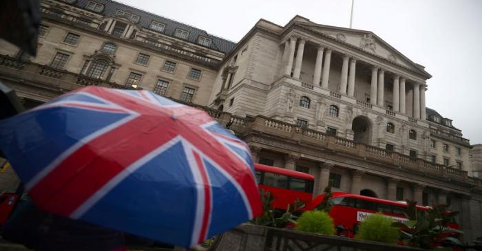 FILE PHOTO: A pedestrian shelters under an umbrella in front of the Bank of England, in London