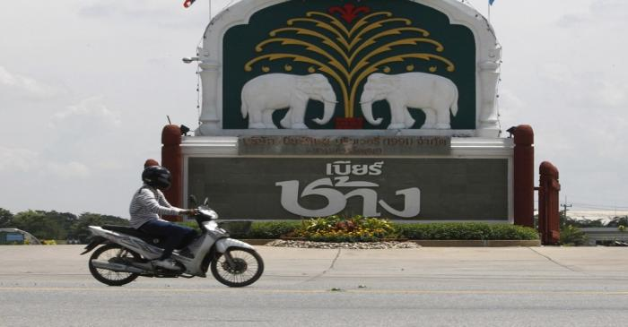 A man rides his motorcycle past a beer factory belonging to Thai Beverage in Ayutthaya province