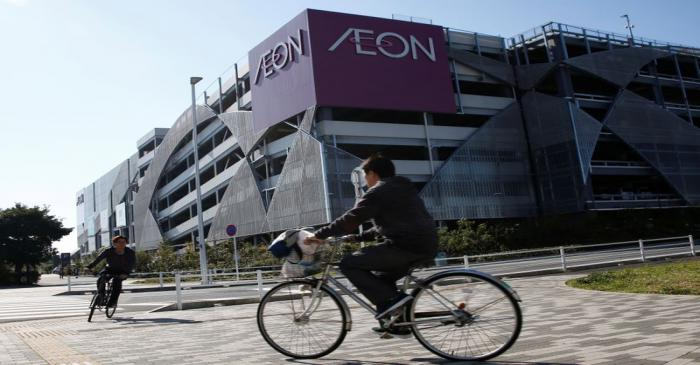 People riding bicycles drive past Aeon Co Ltd's shopping mall in Chiba