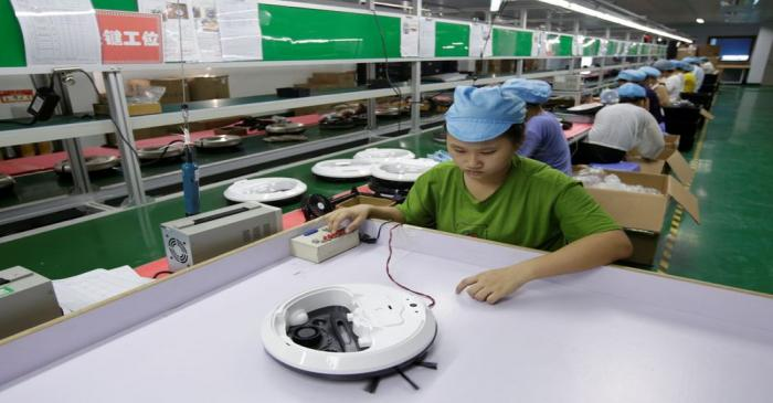 FILE PHOTO: An employee works on the production line of a robot vacuum cleaner at a factory of