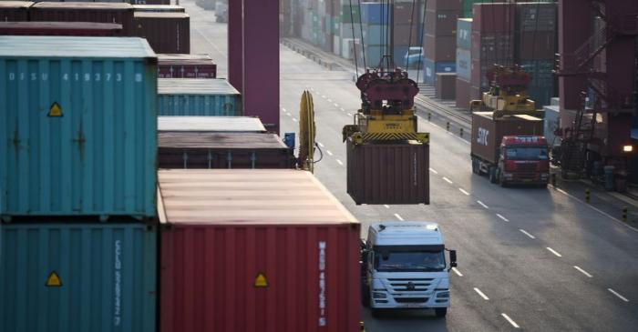 Trucks transport shipping containers at Qianwan container terminal of Qingdao port in Qingdao