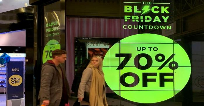 FILE PHOTO: People walk past a sign advertising Black Friday offers at a perfume store in