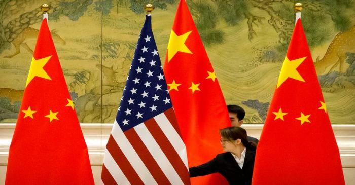 FILE PHOTO: Chinese staff members adjust U.S. and Chinese flags before the opening session of