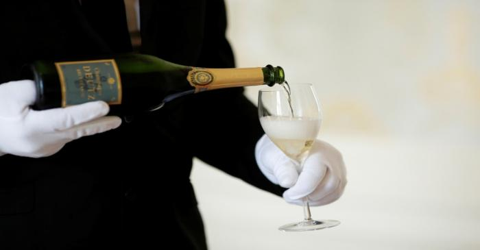 FILE PHOTO: An employee serves a glass of Champagne during the traditional wine harvest at the