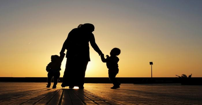 FILE PHOTO: A woman walks with her two children at sunset near the seashore in Benghazi
