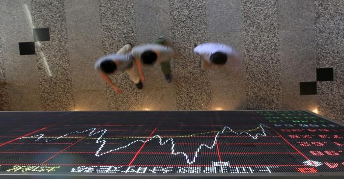 People walk under an electronic board showing stock information at the Shanghai Stock Exchange