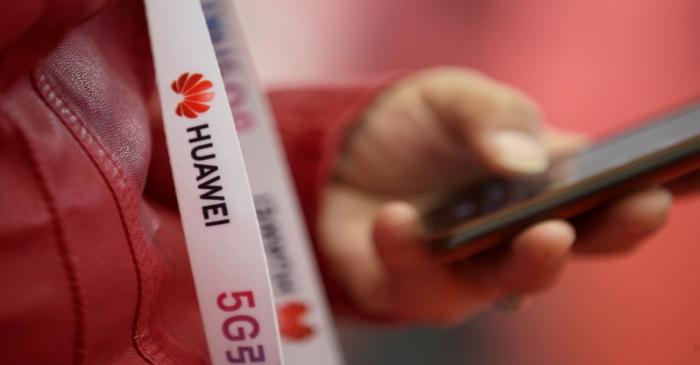 An attendee wears a badge strip with the logo of Huawei and a sign for 5G at the World 5G