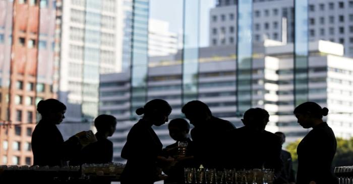 Butlers prepare for drinks inside a banqueting hall at a hotel in Tokyo