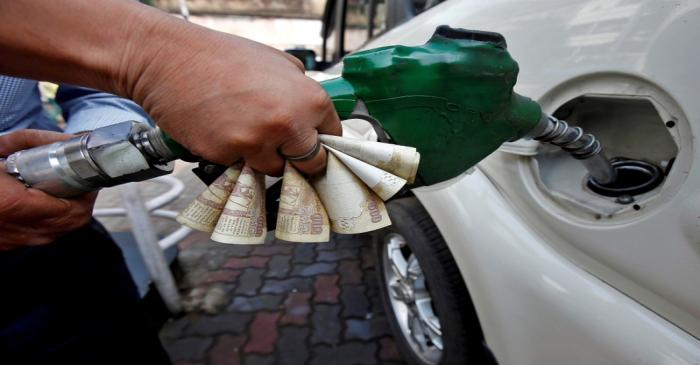 FILE PHOTO: A worker fills diesel in a car as he holds 500 Indian rupee banknotes at a fuel