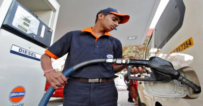 FILE PHOTO: A worker fills a vehicle with diesel at a fuel station in the western Indian city