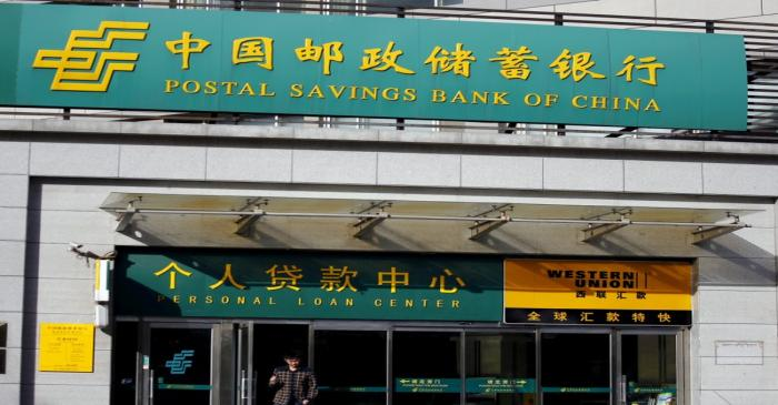 FILE PHOTO: Man walks out of a Postal Savings Bank of China branch in Beijing