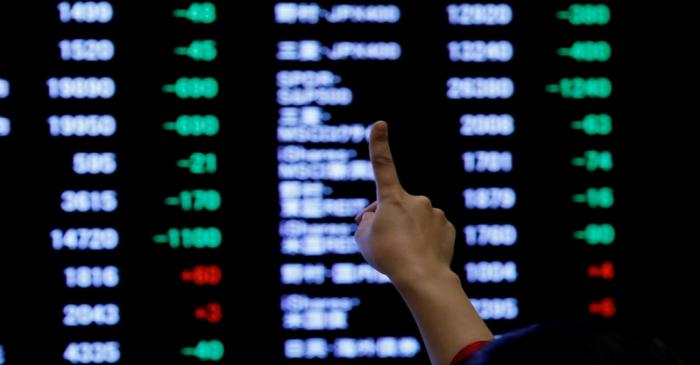FILE PHOTO: A woman points to an electronic board showing stock prices as she poses in front of