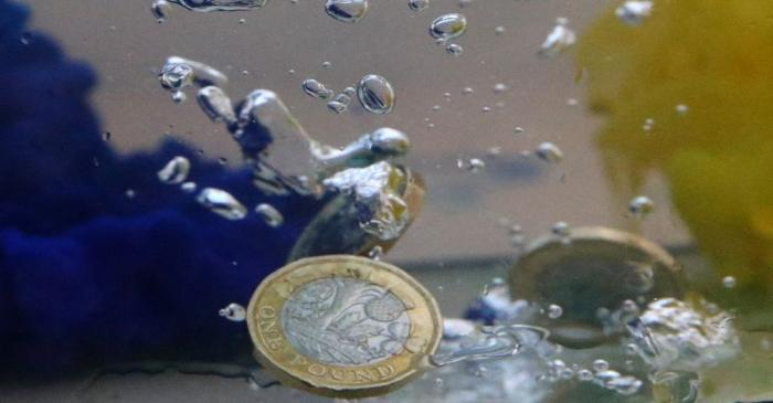 UK pound coins plunge into water coloured with the European Union flag colours in this