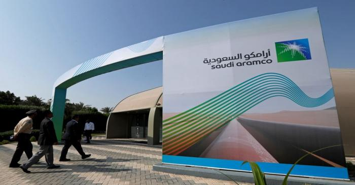 FILE PHOTO: Logo of Aramco is seen as security personnel walk before the start of a press