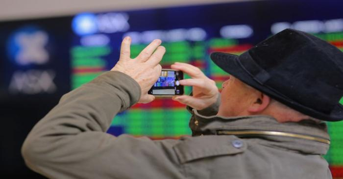 An investor takes a photograph using his phone as he stands in front a board displaying stock