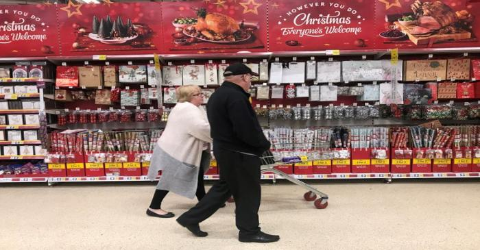 FILE PHOTO: A woman pushes a shopping trolley past Christmas decorations for sale in a Tesco