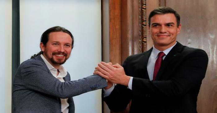 FILE PHOTO: Spain's acting PM Sanchez and Unidas Podemos leader Iglesias present their
