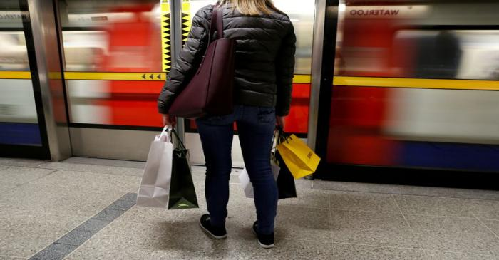 FILE PHOTO: A woman carries her shopping bags before boarding a train on the London Underground