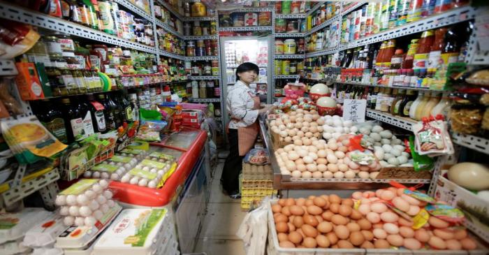 A vendor is seen in her store at a supermarket in downtown Beijing