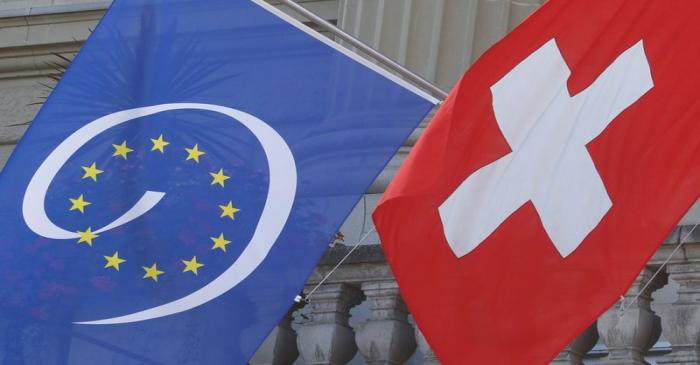 FILE PHOTO:  Switzerland's national flag flies beside the one of the Council of Europe at the