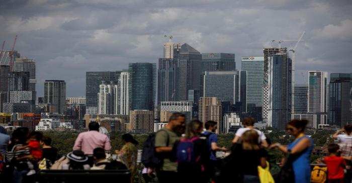 People look out onto the Canary Wharf financial district as they stand at a viewing area in