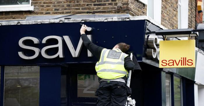 A worker puts up at Savills estate agents sign in London