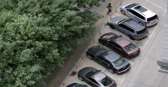 A woman walks past cars in Beijing