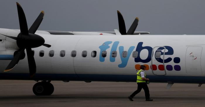 FILE PHOTO: An airport worker examines a flybe aircraft before it takes off from Liverpool John