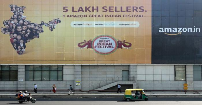 FILE PHOTO: People move past a hoarding of Amazon India outside a metro rail station in New