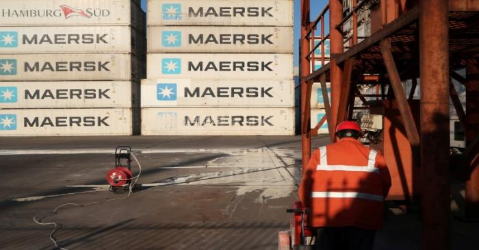 FILE PHOTO: Worker is seen next to Maersk shipping containers at a logistics center