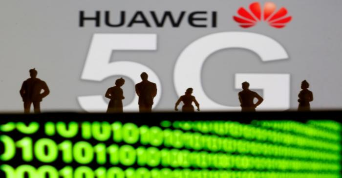 FILE PHOTO: Small toy figures are seen in front of a displayed Huawei and 5G network logo in