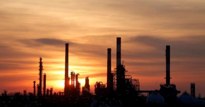 FILE PHOTO: The sun sets behind the chimneys of the Total Grandpuits oil refinery southeast of