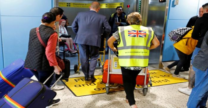 FILE PHOTO: An official assists passengers at Manchester Airport, Britain