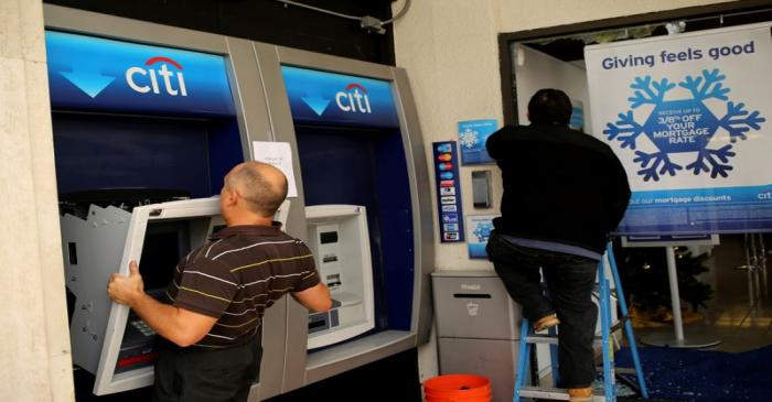 FILE PHOTO: A worker replaces an ATM machine at a bank building on  Shattuck Avenue, in