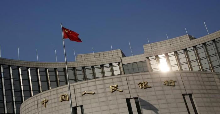 A Chinese national flag flies at the headquarters of the People's Bank of China, the country's