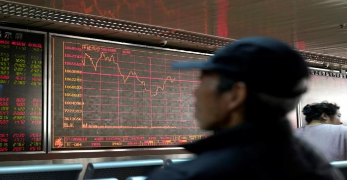 An investor looks at a stock quotation board at a brokerage office in Beijing