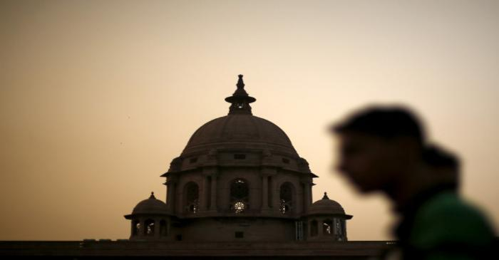 FILE PHOTO: A commuter walks past the building of India's Ministry of Finance during dusk in