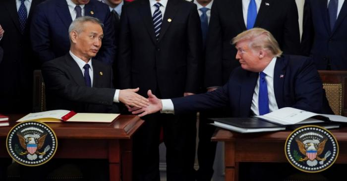 Chinese Vice Premier Liu He and U.S. President Donald Trump shake hands after signing