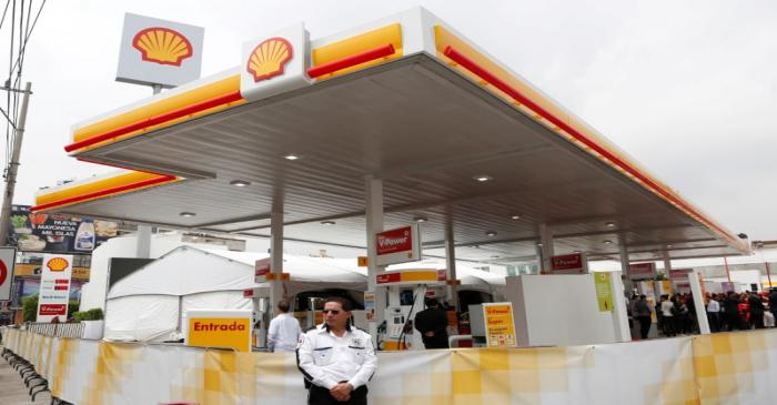FILE PHOTO: A guard stands outside Anglo-Dutch oil major Royal Dutch Shell's first gas station
