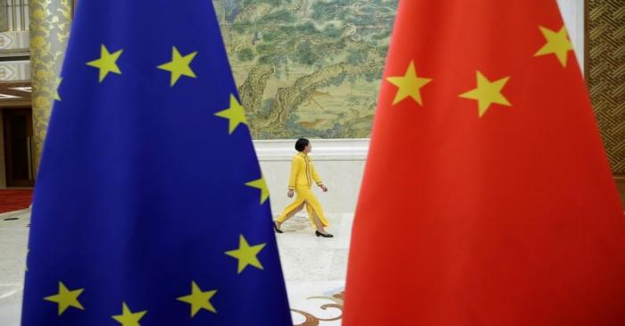 An attendant walks past EU and China flags ahead of the EU-China High-level Economic Dialogue