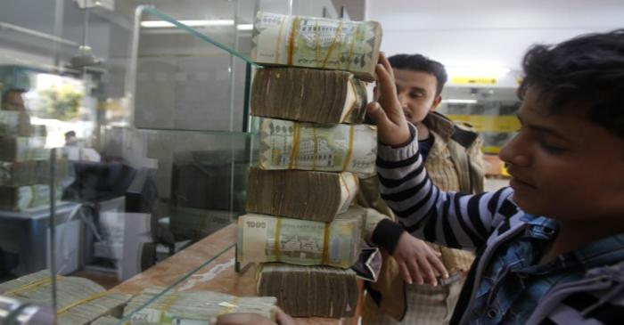 A customer receives bundles of Yemeni Riyal banknotes at an exchange company in Sanaa