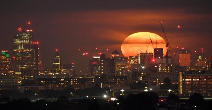 The full moon is seen rising behind skyscrapers at Canary Wharf and the London skyline, London,