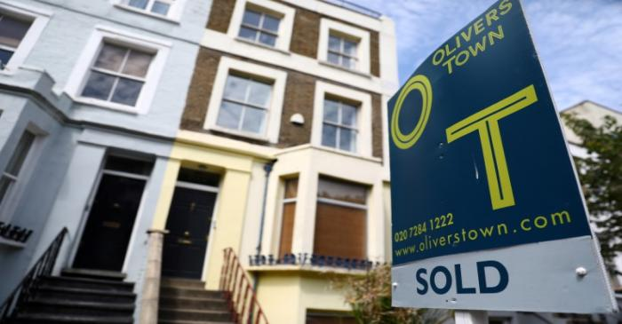 FILE PHOTO: An estate agent board is displayed outside a property in London